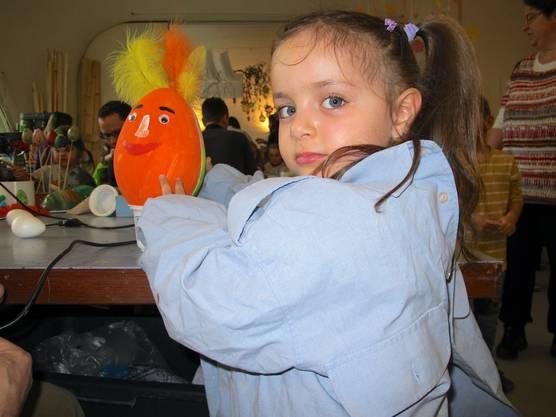 Sophia bastelt ein orangenes Ei mit Federn und Augen.