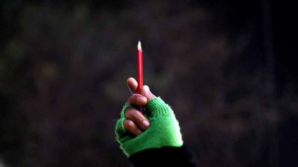 Eine Frau hält zum Gedenken an die im Januar 2015 von Terroristen getöteten Journalisten der Pariser Satirezeitung Charlie Hebdo einen Bleistift in die Höhe (Archiv)
