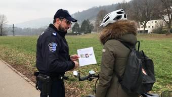 Mit den Medien im Schlepptau: Polizisten verteilen am Montagvormittag an der Aare Flugblätter und sprechen Passanten an.