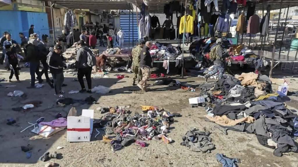 Menschen und Sicherheitskräfte gehen in der irakischen Hauptstadt am Ort eines tödlichen Anschlags, einem Markt, auf dem gebrauchte Kleidung verkauft wurde, an auf dem Boden verstreuten Kleidung und Schuhen vorbei. Foto: Hadi Mizban/AP/dpa