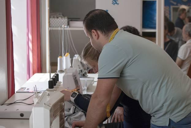 Dekorationsschneider Samer Mohammad  hilft bei der Bedienung der Overlock