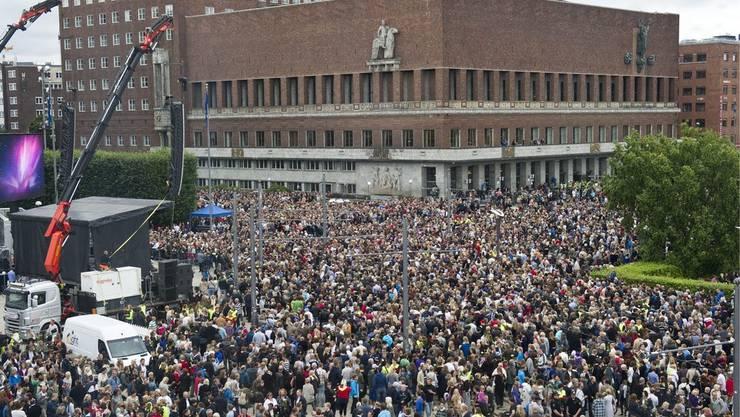 Tausende Menschen versammeln sich am Montag vor der City Hall in Oslo, um an einem Rosenmarsch teilzunehmen
