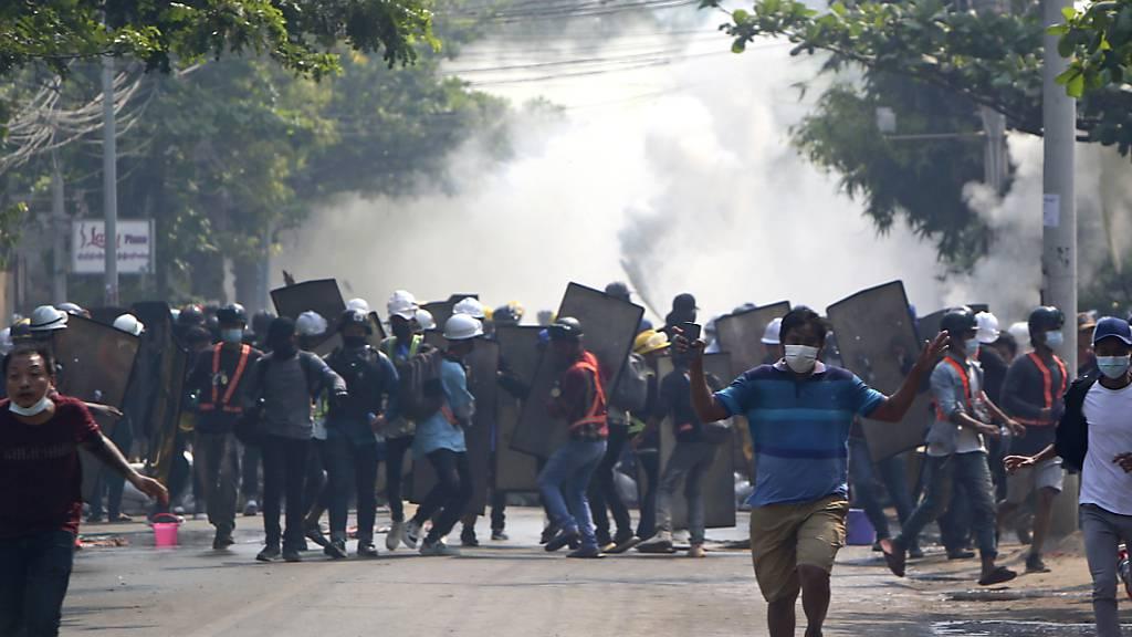 Demonstranten rennen in Mandalay vor Tränengas davon. Foto: Uncredited/AP/dpa
