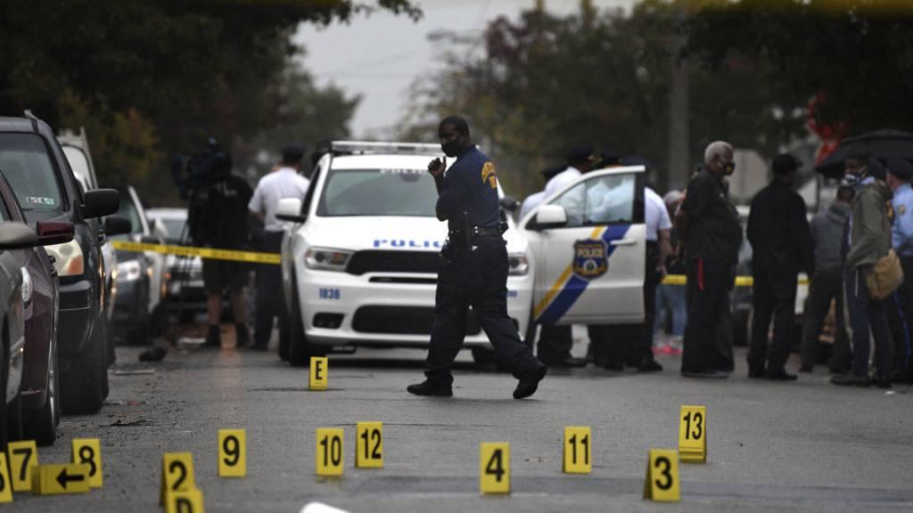Menschen stehen während laufender Ermittlungen an einer Straße, an der am 26.10.2020 ein 27-jähriger Schwarzer von Polizisten erschossen wurde. Der Mann sei mit einem Messer bewaffnet gewesen und habe dieses trotz mehrfacher Aufforderungen nicht fallen lassen, erklärte ein Polizeisprecher. Foto: Tom Gralish/The Philadelphia Inquirer/AP/dpa