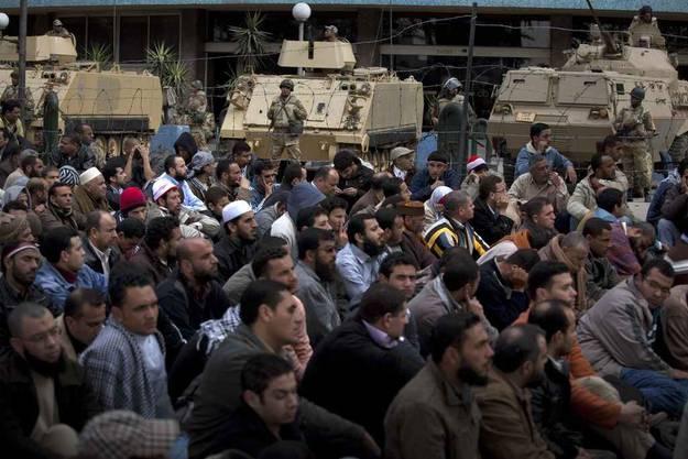 Demonstranten im Vordergrund, Armeepanzer im HIntergund