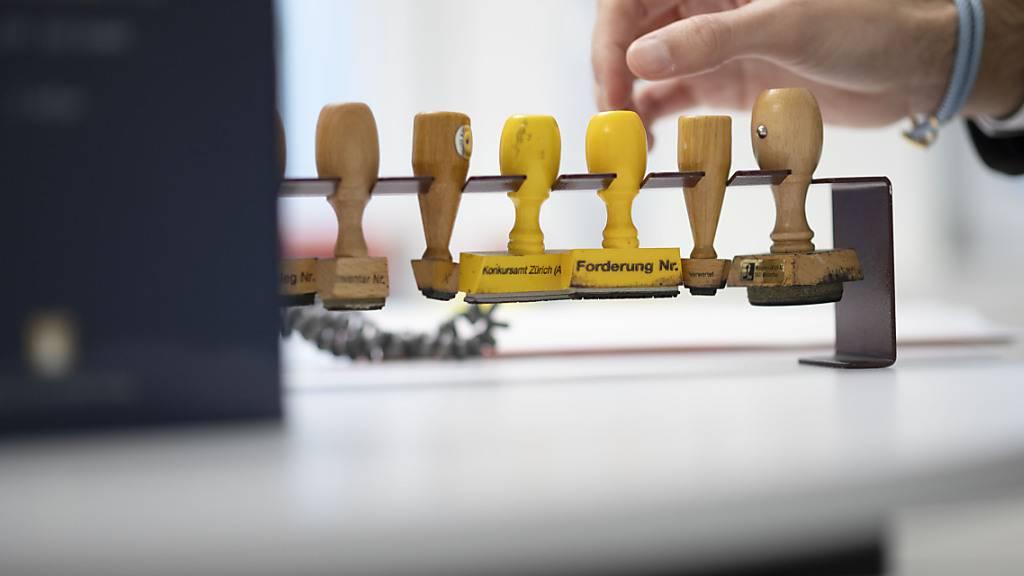 Ein Mitarbeiter des Konkursamtes Zürich greift zu einem Stempel im Stempelhalter. (Symbolbild)