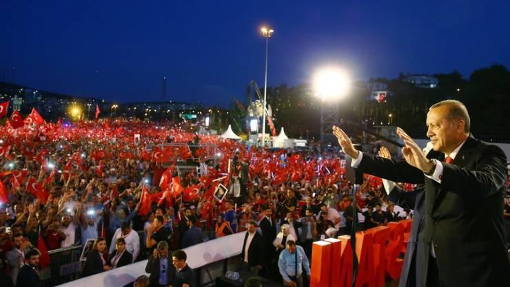 Der türkische Präsident Erdogan begrüsst bei einer Gedenkveranstaltung auf einer Bosporusbrücke in Istanbul seine Anhänger.