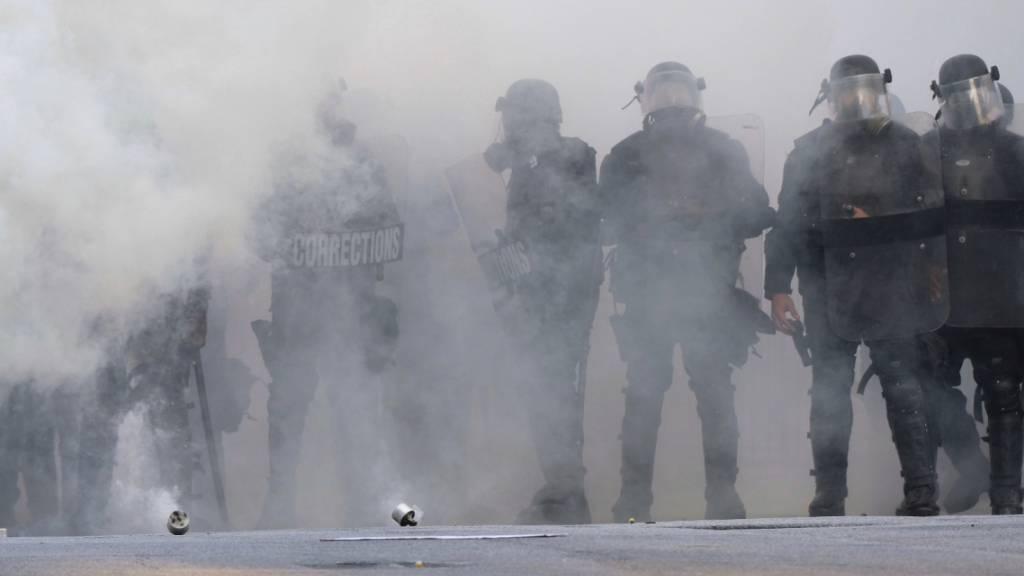 dpatopbilder - Polizisten stehen während eines Protests in Atlanta inmitten einer Tränengaswolke. Foto: Ben Gray/Atlanta Journal-Constitution/AP/dpa