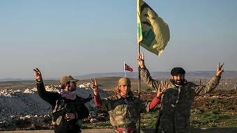 Mitglieder der kurdischen Volksschutzeinheiten (YPG) schwenken ihre gelbe Flagge.
