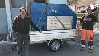 Gemeinderat Samuel Schmid (l.) und Bauamtsleiter Werner Tischler nehmen die Maschine samt Anhänger in Empfang.