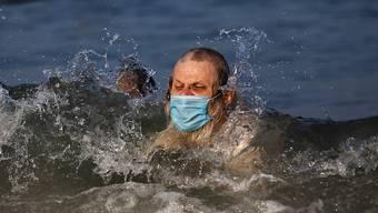 Ein Mann schwimmt mit Mundschutz. (Symbolbild)