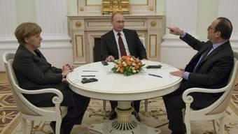 Hollande, rechts, gestikuliert im Gespräch mit Putin und Merkel