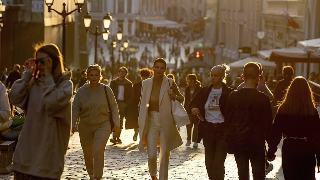 Menschen, die meisten von ihnen ohne Mund-Nasen-Schutz, spazieren bei warmem Wetter während eines Sonnenuntergangs im Zentrum von Moskau. Foto: Alexander Zemlianichenko/AP/dpa