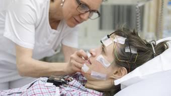 Hightech im Schlaflabor: Liliane Weber befestigt die nötigen Sensoren und Messgeräte an Journalistin Sibylle Saxer.
