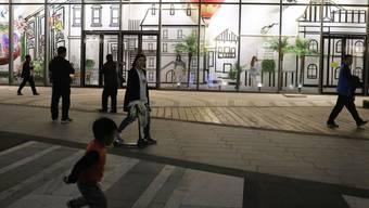 Passanten vor der Wanda Mall, einem Kaufhaus, das zur neu eröffneten Wanda Oriental Movie Metropolis in Qingdao, China, gehört - ein milliardenteurer Mega-Komplex, den Chinas reichster Mann Wang Jianlin finanziert hat.