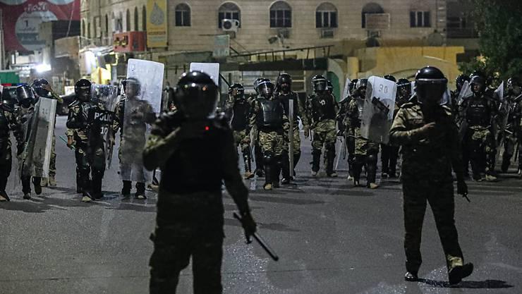 Polizisten versuchen während eines Protests in Basra Demonstranten daran zu verhindern, ein Regionalbüro des Parlaments zu stürmen. Foto: Nabil Al-Jurani/AP/dpa