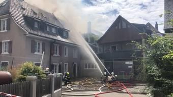 Der Dachstock eines Hauses steht in Flammen.