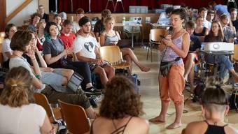 Gebannt hören die Klimajugendlichen in der Plenumsversammlung zu. Zeichensprache und Dolmetscherinnen unterstützen die Diskussionen. (Bild Annette Boutellier)