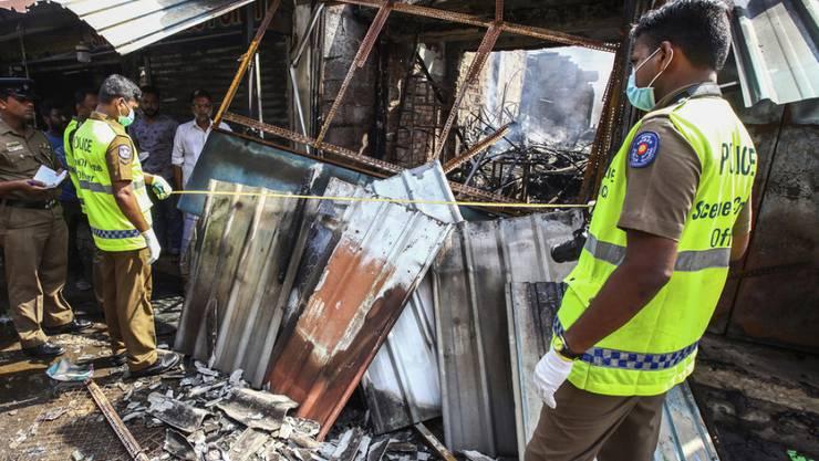 Die Polizei bei einem von dutzenden mutmasslich von Singhalesen zerstörten Läden muslimischer Besitzer in Sri Lanka.