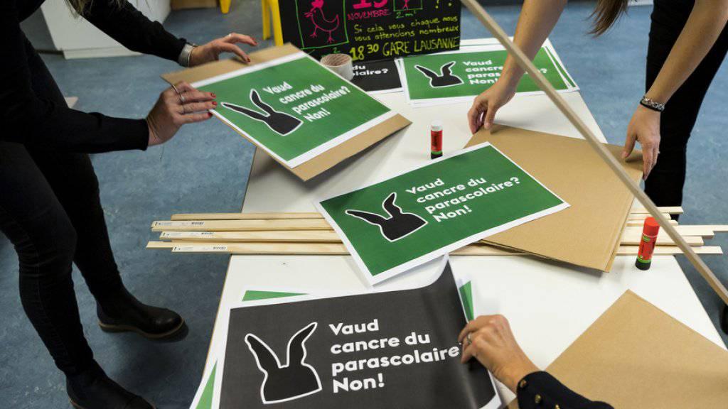 Mitarbeiterinnen einer Kindertagesstätte bereiten Plakate für die Kundgebung in Lausanne vor.