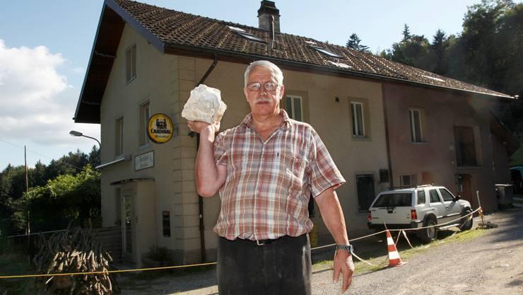 Peter Bieri zeigt die Groesse der Steine die die Sprengschaeden an seinem Haus verursacht haben