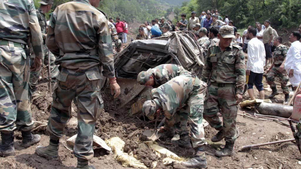 Rettungskräfte am Sonntag bei der Bergung der in einem Erdrutsch getöteten Buspassagiere in Indien.