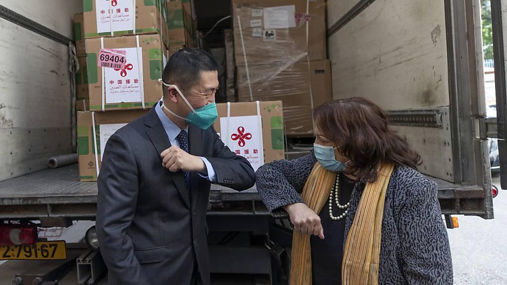 Guo Wei, Leiter des Büros der Volksrepublik China bei der Palästinensischen Autonomiebehörde, und Mai Al-Kaileh, Gesundheitsministerin der Palästinensischen Autonomiegebiete, begrüßen sich vor einem Lastwagen mit einer Ladung von Dosen des Corona-Impfstoffs des chinesischen Herstellers Sinopharm mit dem Ellbogen. Foto: Nasser Nasser/AP/dpa