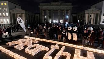 Kerzen brennen vor dem im Dunkeln stehenden Brandenburger Tor in Berlin: Zur 10. Earth Hour wurden in über 7000 Städten die Lichter an Sehenswürdigkeiten ausgeschaltet. Im Zeichen des Klimaschutzes.