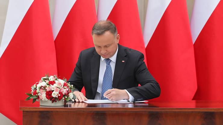 Polen Präsident Andrzej Duda unterzeichnet einen Vorschlag für eine Verfassungsänderung, wonach gleichgeschlechtliche Paare von der Adoption von Kindern ausgeschlossen werden sollen. Foto: Pawel Supernak/PAP/dpa