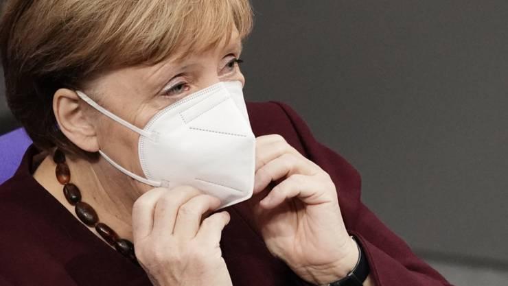 Bundeskanzlerin Angela Merkel setzt sich im Bundestag, nach der Regierungserklärung zur Bewältigung der Corona-Pandemie, ihre Maske auf. Foto: Michael Kappeler/dpa