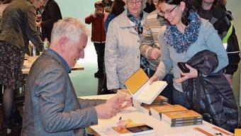 Die Zuhörerinnen und Zuhörer nutzen die Gelegenheit und lassen sich ihr Buch von Röbi Koller signieren.