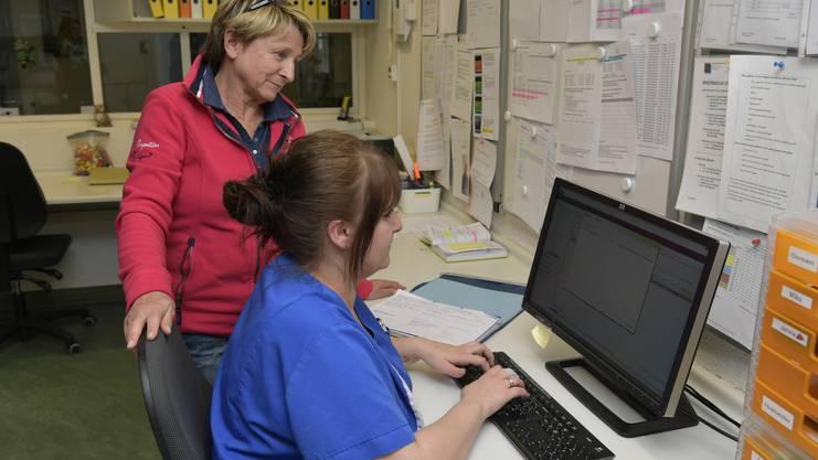 Cécile Boillat, die Leiterin des Pflegedienstes, und eine Mitarbeiterin bei der Eingabe von Patientendaten ins neue System.