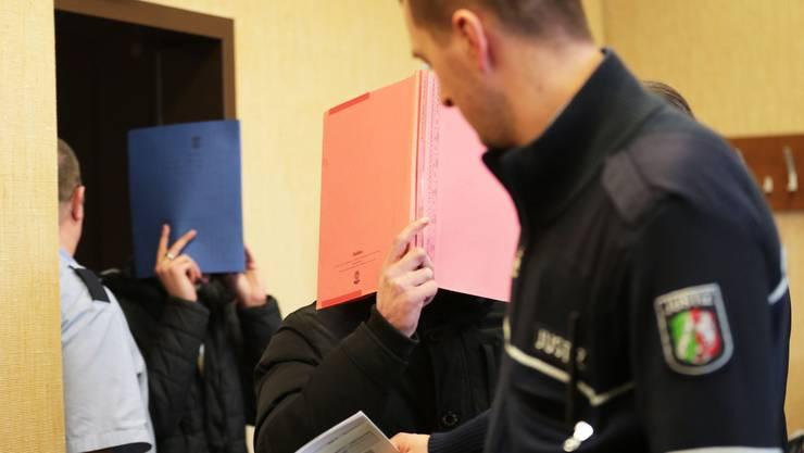 Zwei der drei Angeklagten betreten den Saal des Kölner Amtsgerichts.