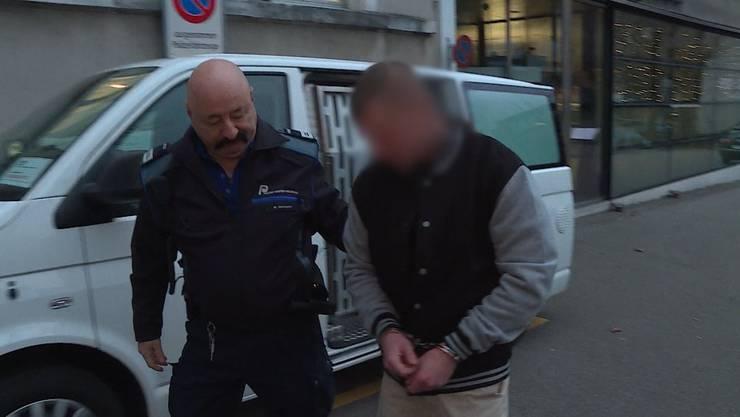 Der Beschuldigte wird von einem Polizisten zur Gerichtsverhandlung geführt.