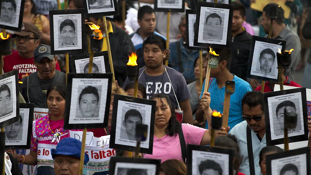 Angehörige und Unterstützer tragen bei einem Protest-Marsch in Mexiko-Stadt im April 2016 Bilder der 43 vermissten Studenten.