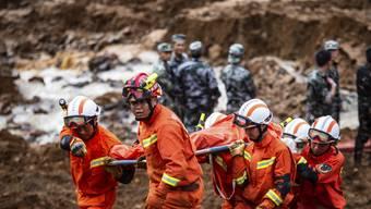 Chinesische Rettungskräfte bergen nach einem grossen Erdrutsch im Südwesten des Landes eine Leiche.