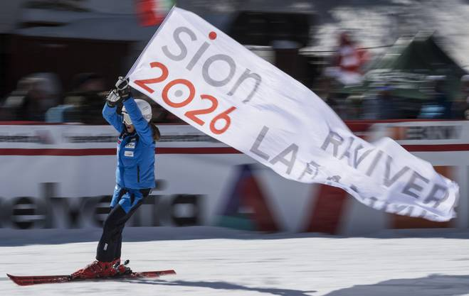 A child enters the the finish area with a banner promoting Olympic Games in Sion 2026, ahead of the women's Alpine Combined Slalom race of the Alpine Skiing FIS Ski World Cup in Crans-Montana, Switzerland, Sunday, March 4, 2018. (KEYSTONE/Alessandro della Valle)