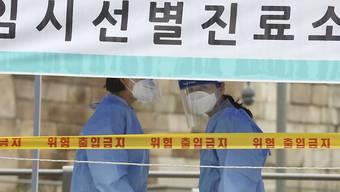 Medizinische Mitarbeiterinnen in Schutzkleidung stehen in einer Einrichtung für Covid-19-Tests in Südkorea. Foto: Ahn Young-Joon/AP/dpa