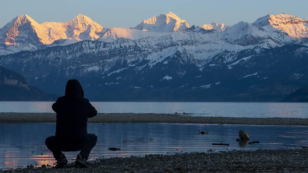 Ein Mann fotografiert das Dreigestirn mit Eiger, Mönch und Jungfrau (von links) das in der Abendsonne leuchtet.