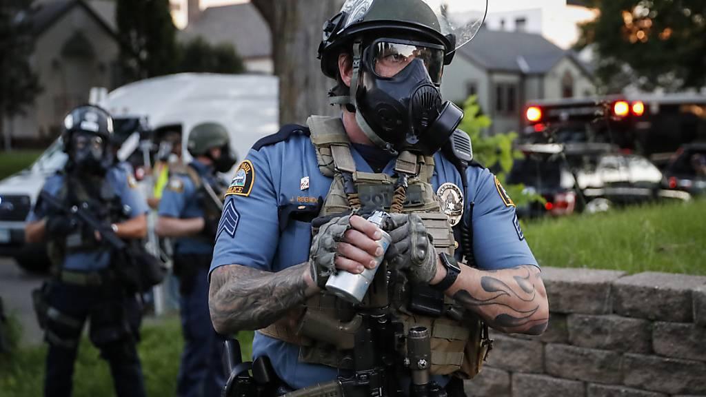Ein Polizeibeamter mit Gasmaske bereitet sich darauf vor, Tränengas gegen Demonstranten einzusetzen während der Proteste nach dem Tod von George Floyd, der in Folge einer brutalen Festnahme durch einen Polizisten in Minneapolis starb. Ein weißer Polizist hatte bei der Festnahme lange auf dem Hals des Afroamerikaners gekniet, welcher mehrmals darauf aufmerksam machte, dass er nicht atmen könne. Foto: John Minchillo/AP/dpa