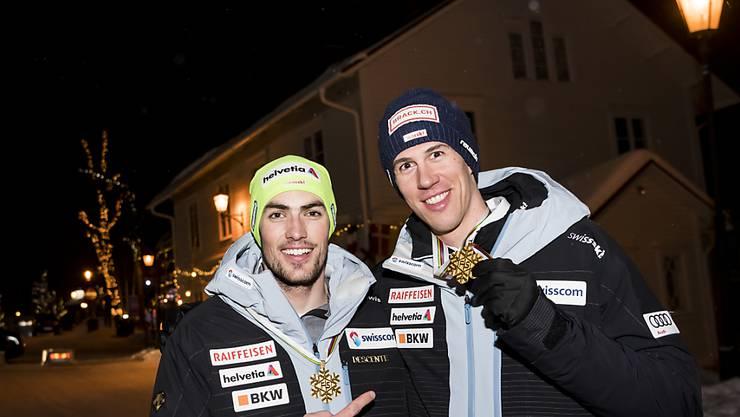 Daniel Yule (links) und Ramon Zenhäusern präsentieren ihre im Team-Wettbewerb gewonnene Goldmedaille