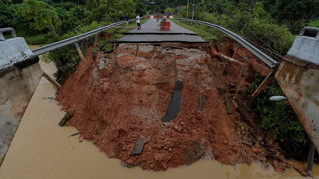 Menschen stehen nahe der Lechar Road Bridge in Dong, die aufgrund von Erdrutschen während anhaltender starker Regenfälle zusammengebrochen ist. Foto: Shafiq Hashim/BERNAMA/dpa