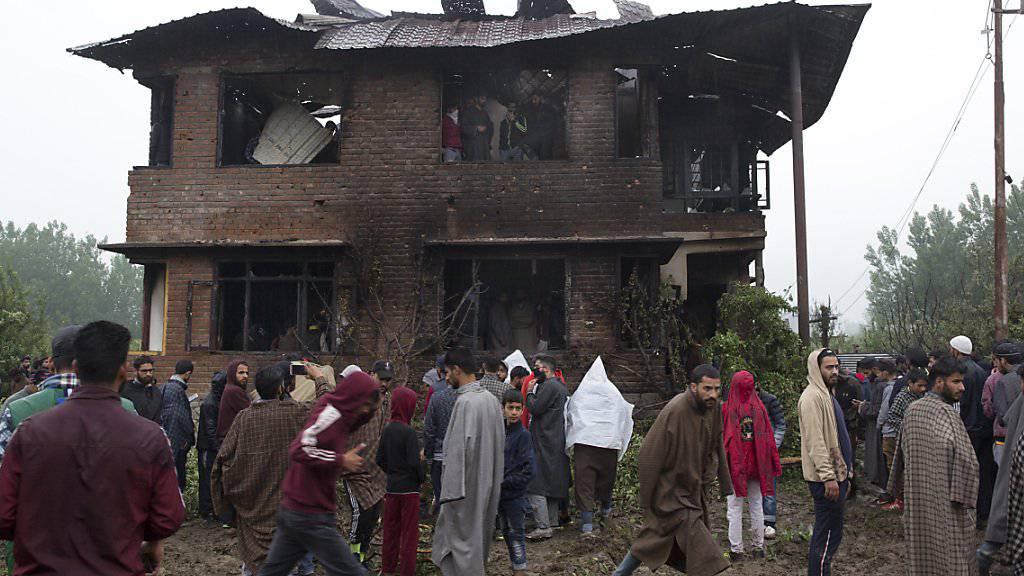 Dorfbewohner versammeln sich nach der Schiesserei vor dem Haus, in dem sich der Kommandant einer Al-Kaida nahmen Organisation verschanzt hatte.