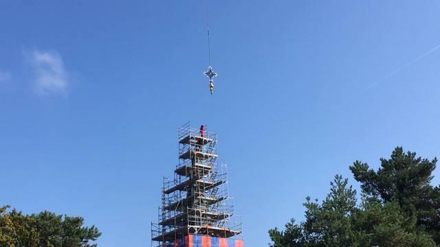 Der Helikopter fliegt das neue Kreuz auf die Würenlinger Kirche.
