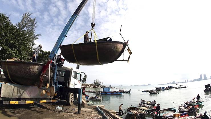 Menschen bewegen Fischerboote in Vorbereitung auf den Sturm Molave. In Vietnam bereiten sich die Behörden darauf vor, 1,2 Millionen Menschen vor einem neuen Tropensturm in Sicherheit zu bringen. Foto: Tran Le Lam/VNA/AP/dpa