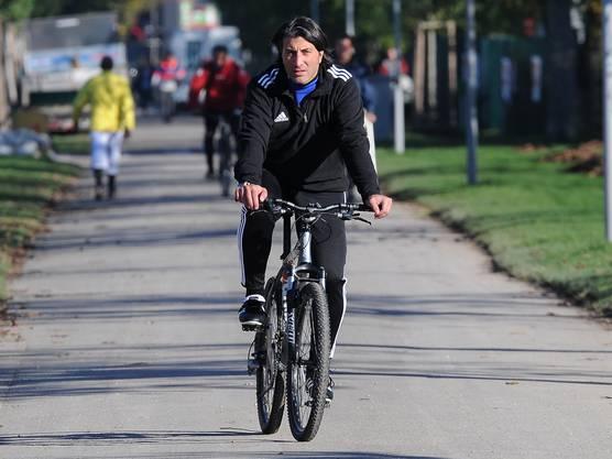 Der neue Trainer rollt mit dem Fahrrad vor.