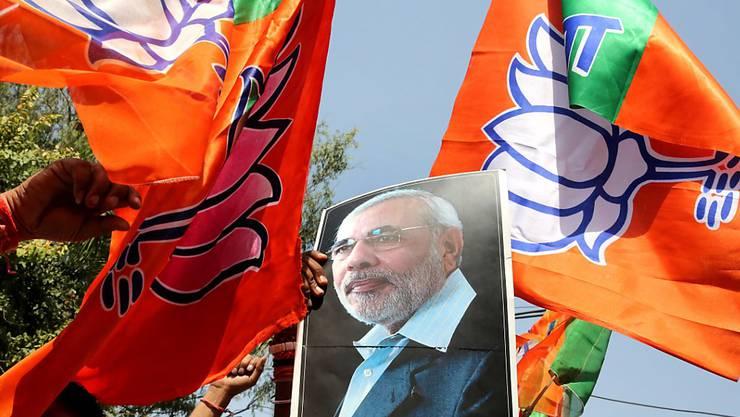 Anhänger von Indiens Regierungschef Narendra Modi feiern mit Fahnen und Modi-Bild ihren Wahlsieg in Uttar Pradesh