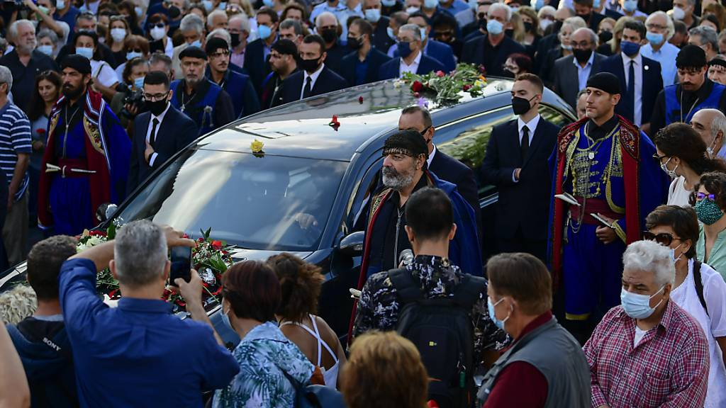 Menschen eskortieren einen Leichenwagen vor der Beerdigung des verstorbenen griechischen Komponisten Mikis Theodorakis. Theodorakis starb am 2. September 2021 im Alter von 96 Jahren. An diesem Donnerstag haben Tausende Kreter von dem Komponisten Abschied genommen. Foto: Michael Varaklas/AP/dpa