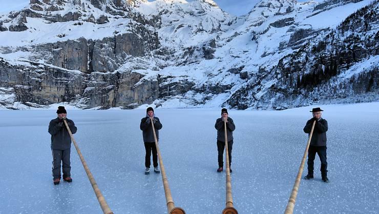 Diese Alphorngruppe wagte sich bereits aufs Glatteis. Ab Samstag ist der Oeschinensee für alle frei zum Eislaufen.