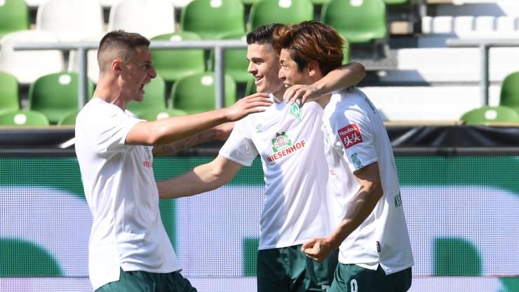 Werders Yuya Osako (r) jubelt mit Milot Rashica und Marco Friedl (l) über sein Tor zum 5:0.